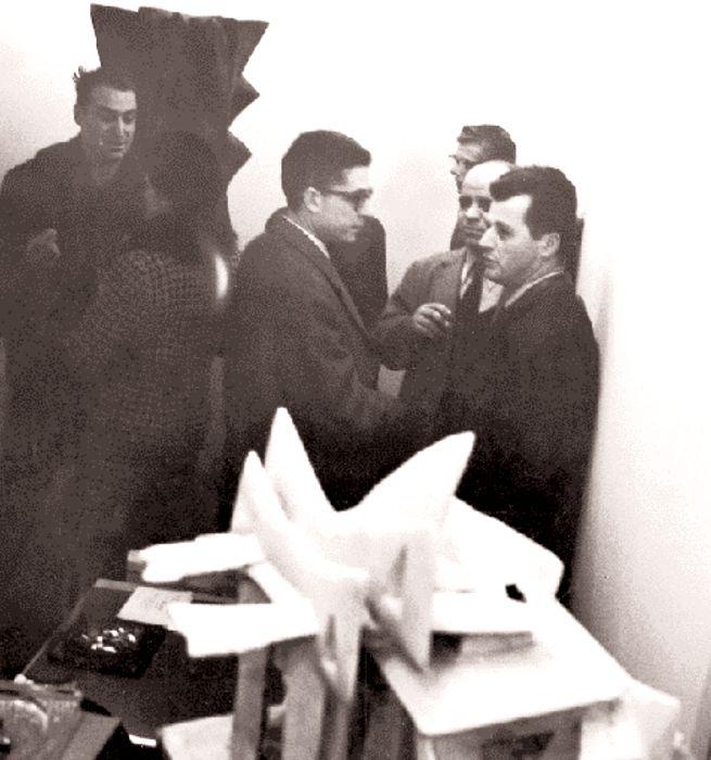 O Γεράσιμος Σκλάβος και ο Kριστιάν Zερβός σε πρώτο πλάνο, στα εγκαίνια της ατομικής του έκθεσης στην γκαλερί Cahiers–Dars, στο Παρίσι, το 1965.