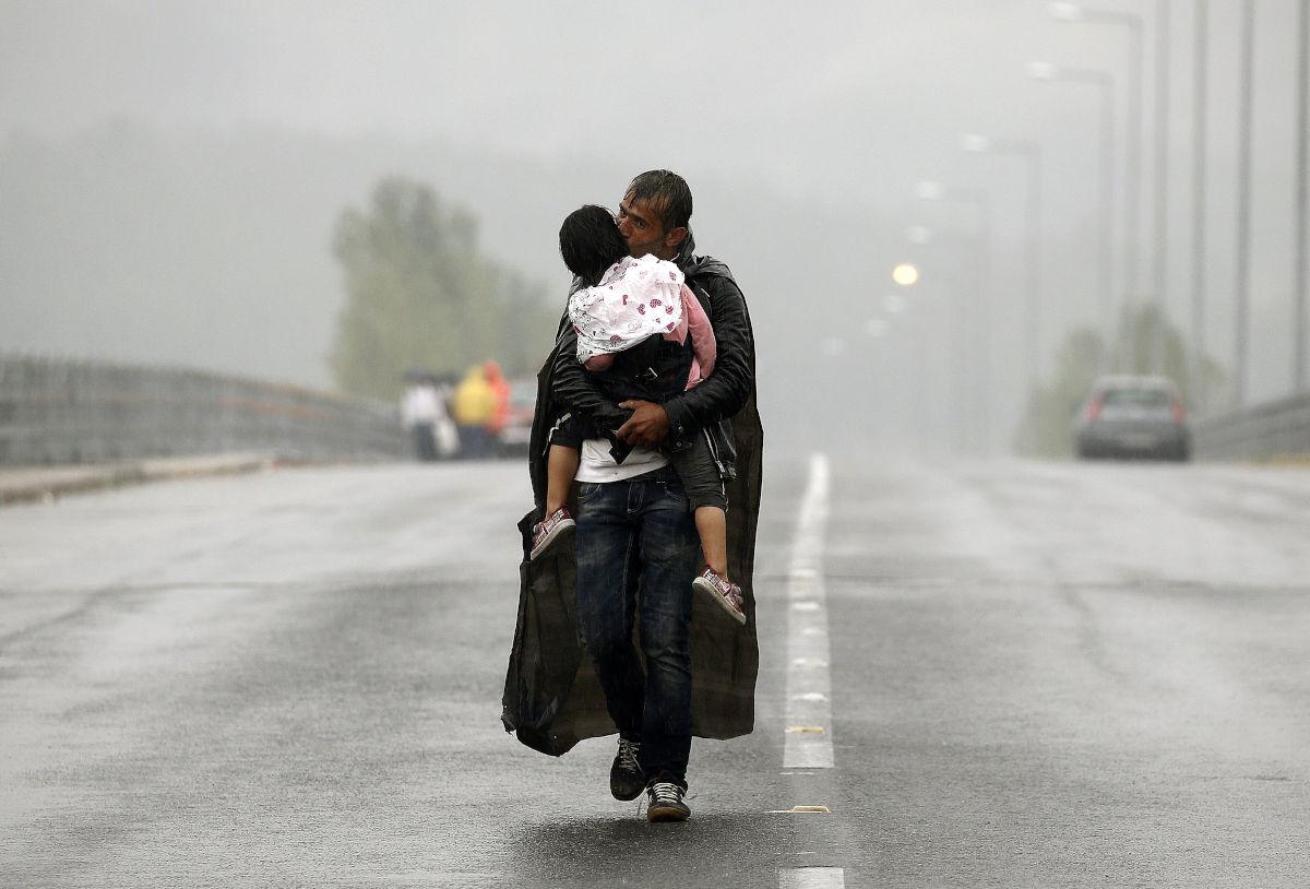 Πρόσφυγας κρατάει σφιχτά το παιδί του στη βροχή στα σύνορα Ελλάδας - Βόρειας Μακεδονίας. Η φωτογραφία βραβεύτηκε με Πούλιτζερ