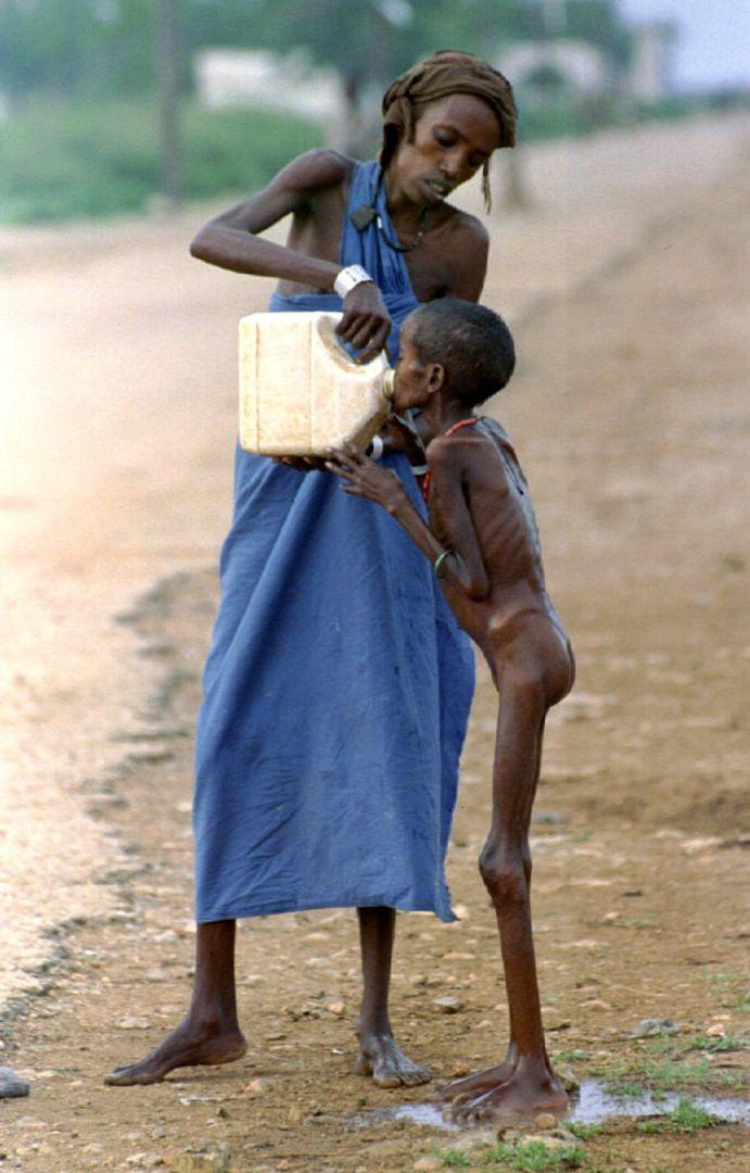 Μια γυναίκα δίνει νερό σε παιδί που λιμοκτονεί στη Σομαλία