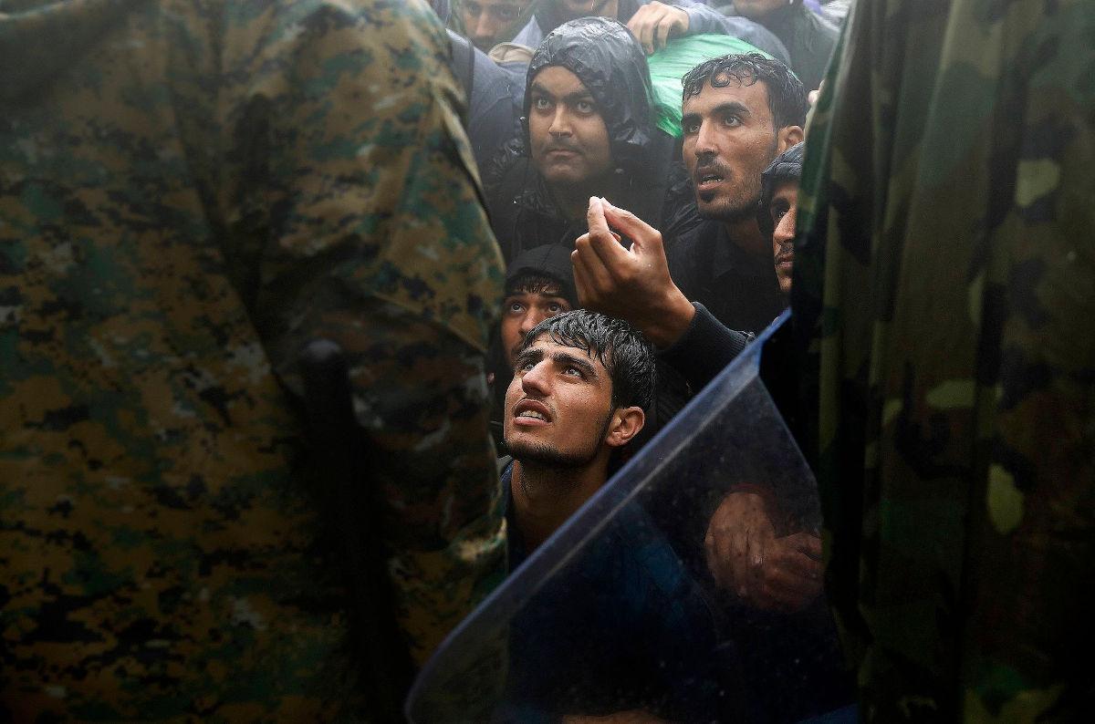 Μετανάστες και πρόσφυγες ικετεύουν τους αστυνομικούς να τους αφήσουν να περάσουν τα σύνορα από την Ελλάδα στη Βόρεια Μακεδονία κατά τη διάρκεια καταιγίδας, κοντά στην Ειδομένη