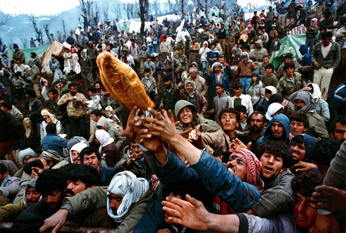 Κούρδοι πρόσφυγες παλεύουν να αρπάξουν ένα καρβέλι ψωμί κατά τη διάρκεια της διανομής ανθρωπιστικής βοήθειας στα σύνορα Ιράκ-Τουρκίας